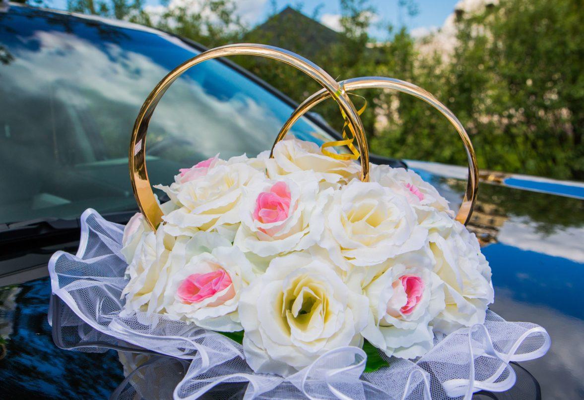Украшение на машину в кремовых тонах, с крупными цветами и золотыми кольцами.