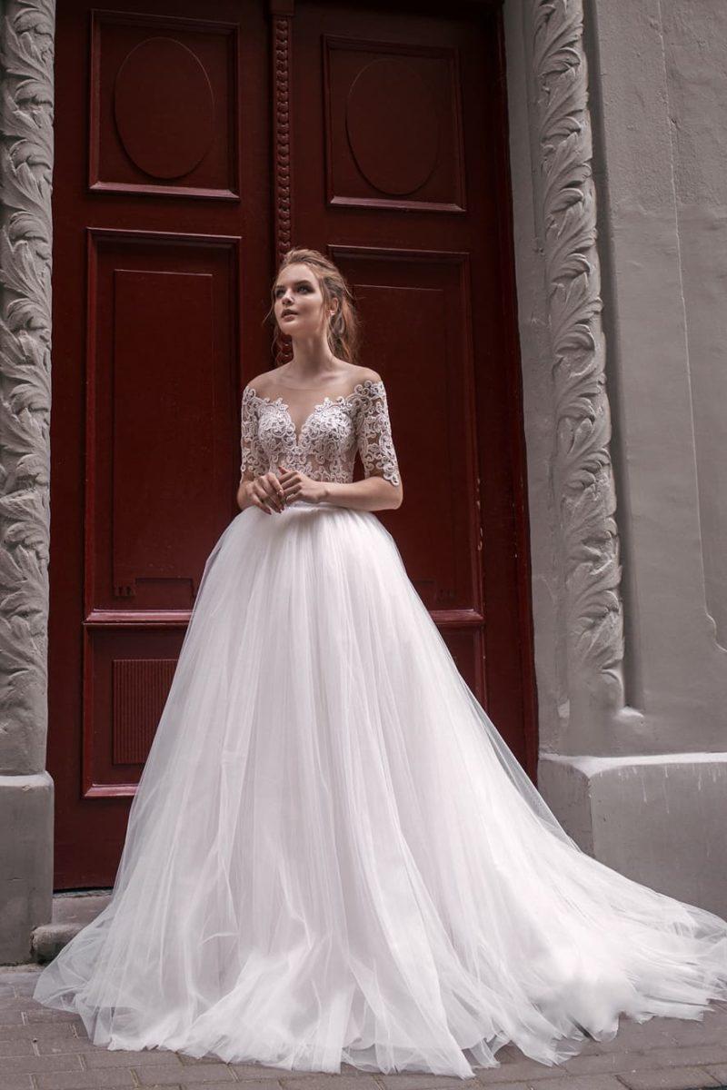 Пышное свадебное платье с открытым верхом и широким поясом на линии талии.