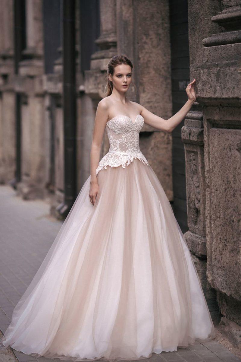 Открытое свадебное платье А-силуэта в бело-бежевых тонах, украшенное кружевом.