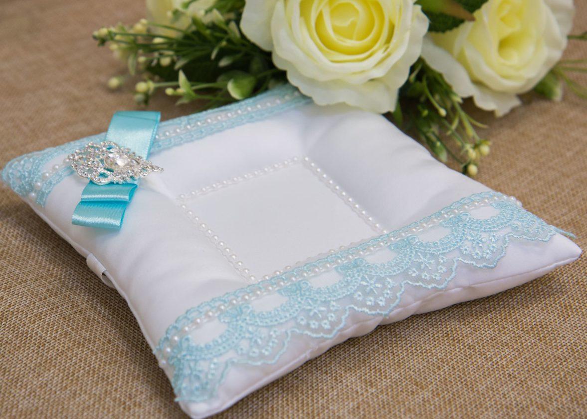 Белая подушечка для колец, украшенная голубым кружевом и стильным бантом.