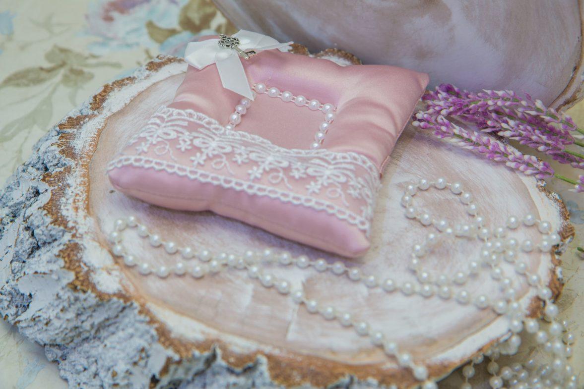 Розовая подушечка для колец, декорированная полосой кружева и белым бантом.