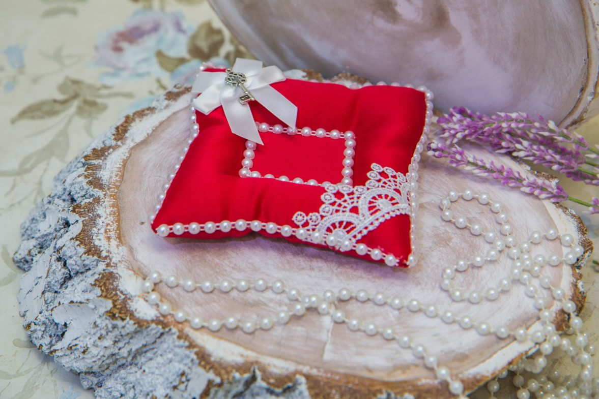 Красная атласная подушечка для колец с отделкой белыми бусинами, кружевом и бантом.