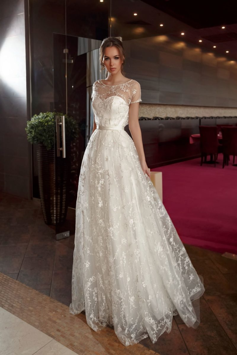 Пышное свадебное платье с полупрозрачным верхом с нежной кружевной отделкой.