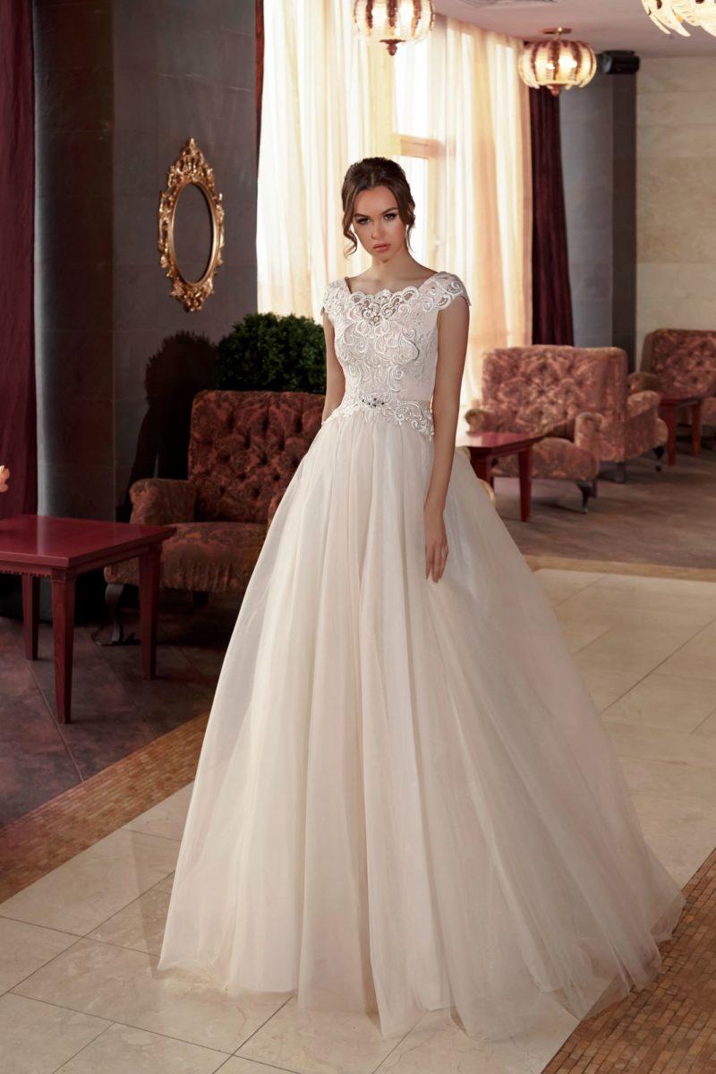 Бежевое свадебное платье пышного кроя с закрытым лифом, украшенным кружевом.