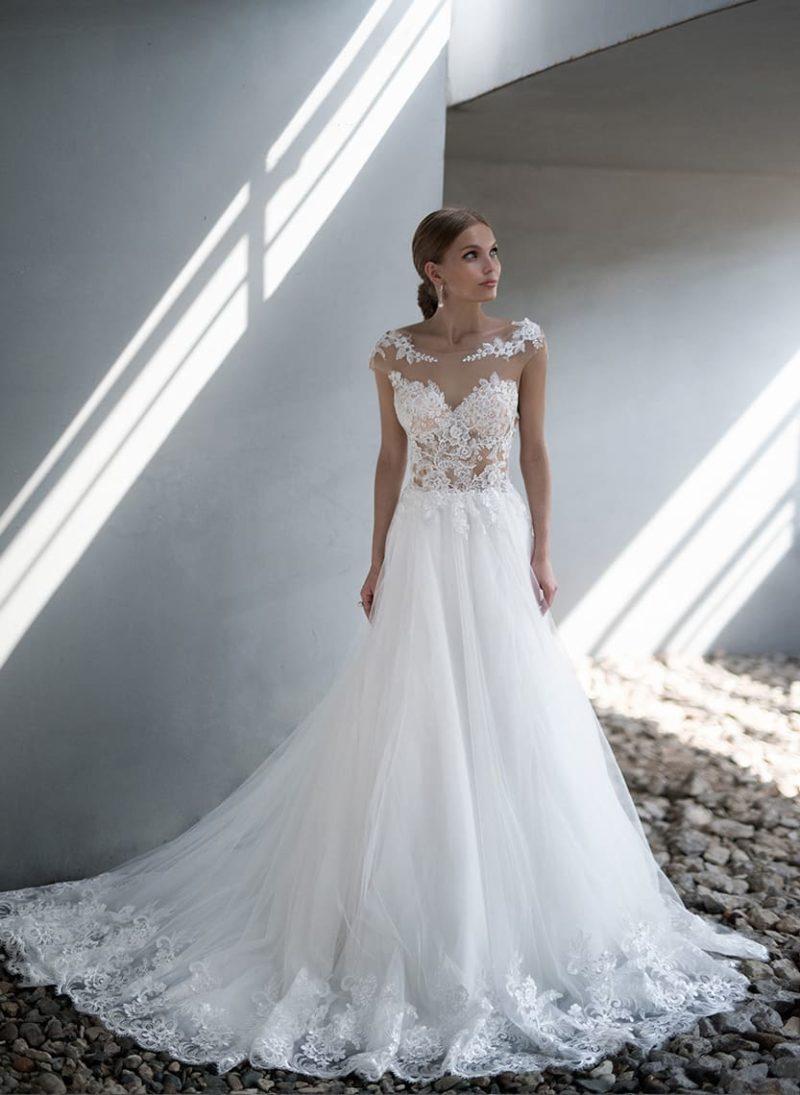 Романтичное свадебное платье с полупрозрачной спинкой и кружевным декором.