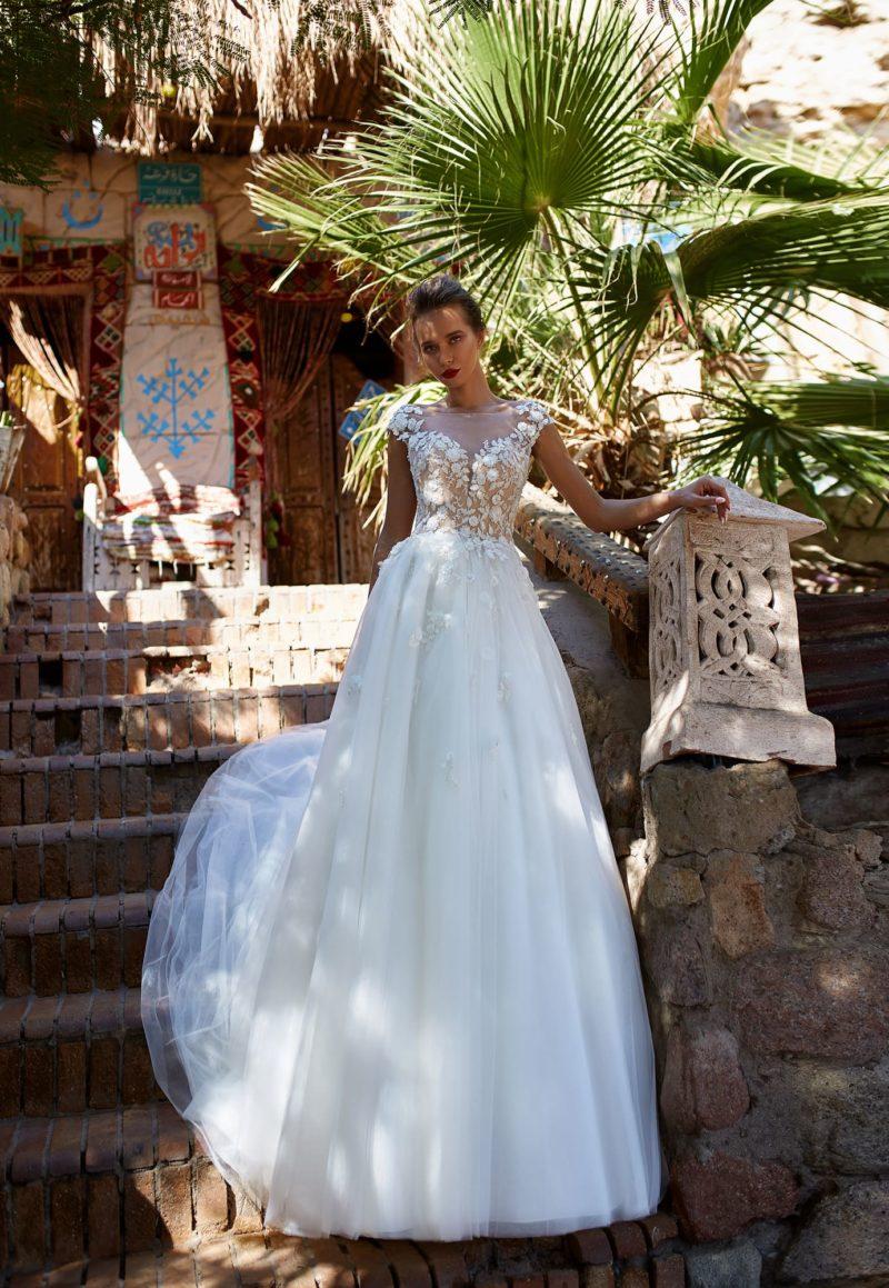 Свадебное платье с кружевными аппликациями по бежевому лифу.