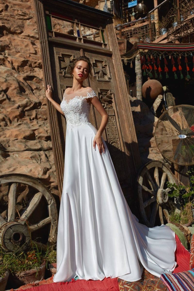 Прямое свадебное платье со шлейфом и фигурными бретелями.