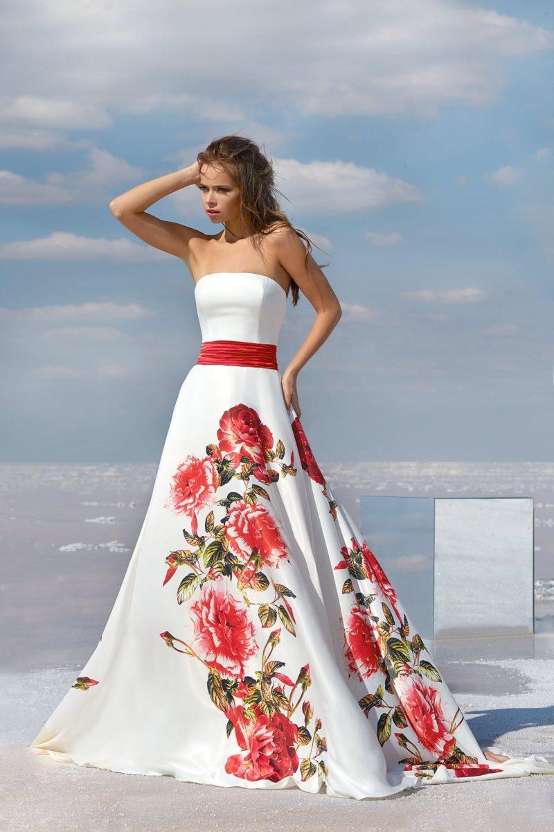Белое вечернее платье с ярким рисунком на ткани и широким красным поясом.