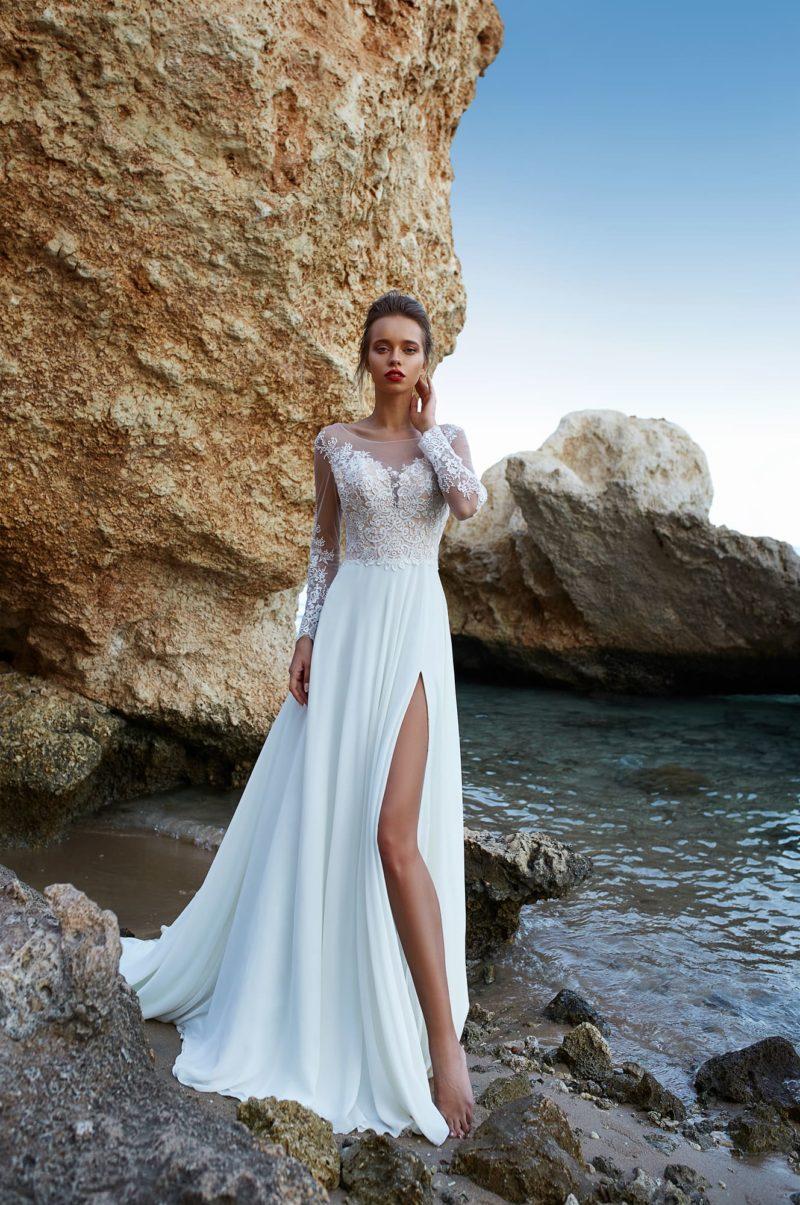Свадебное платье с разрезом на юбке и полупрозрачными рукавами.