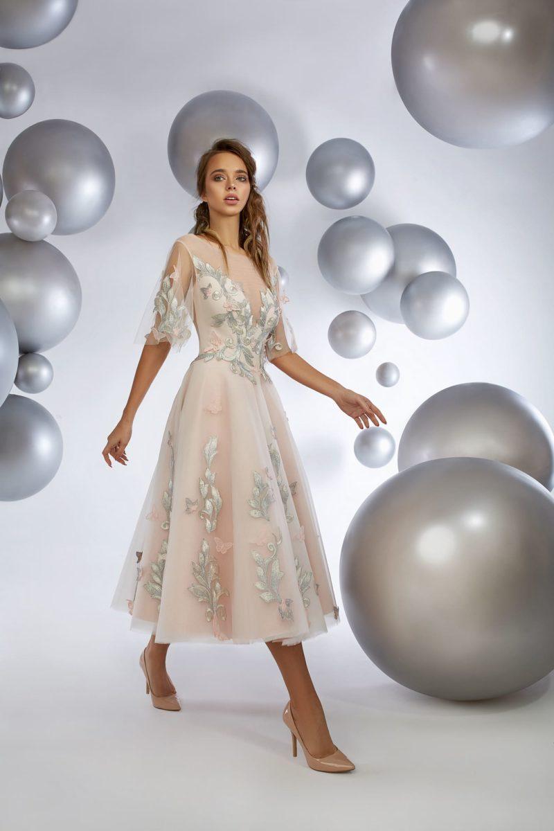 Розовое вечернее платье длиной миди с отделкой серебристыми аппликациями.