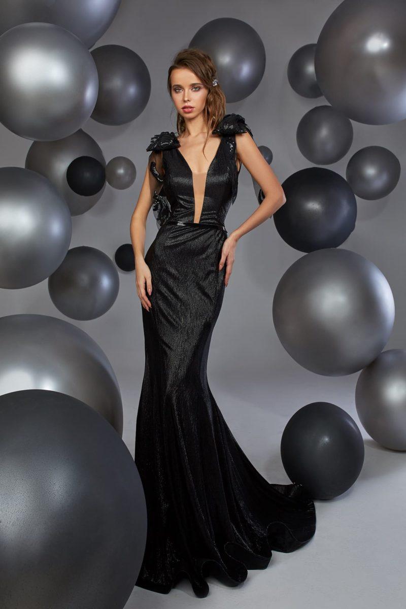 Черное вечернее платье облегающего кроя из сияющей ткани.