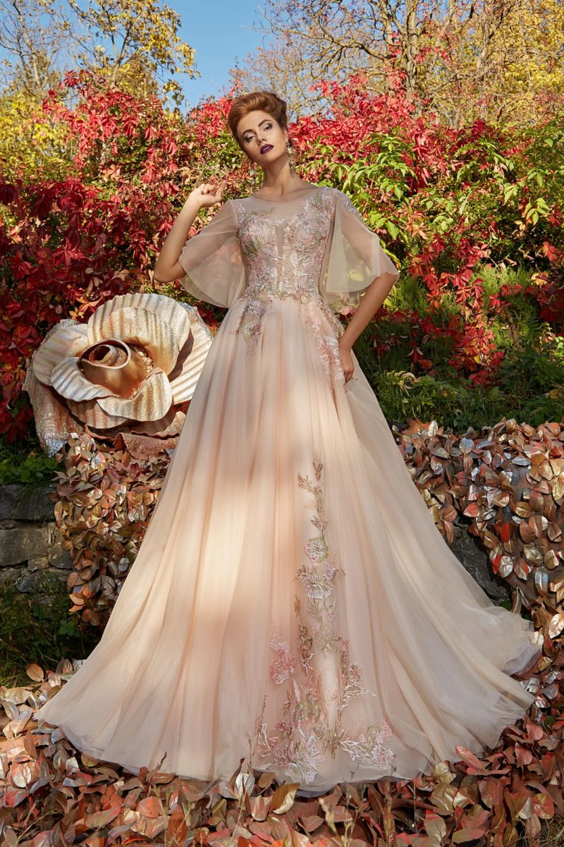 Персиковое вечернее платье с широким рукавом и отделкой аппликациями.