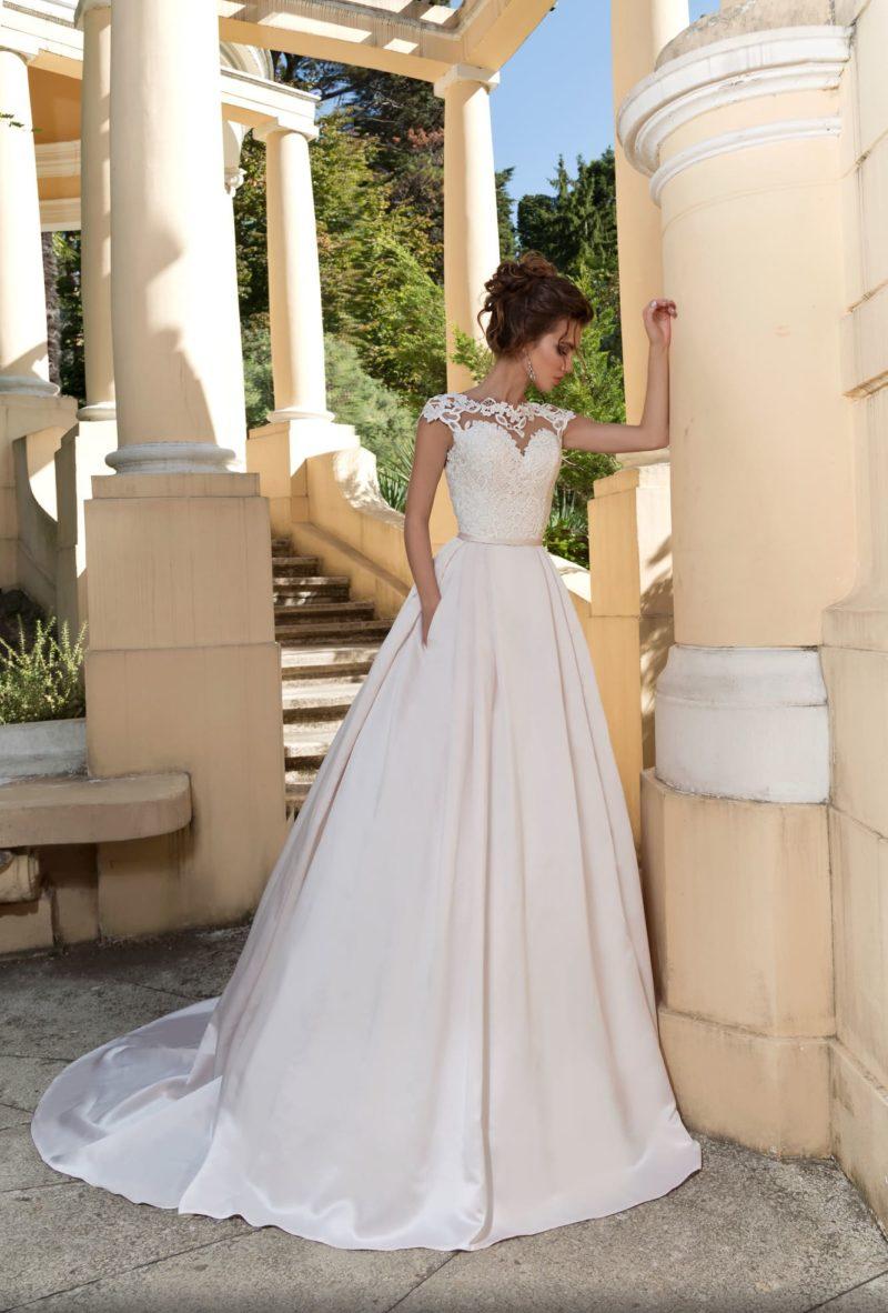 Пышное свадебное платье с элегантным кружевным верхом и узким поясом.