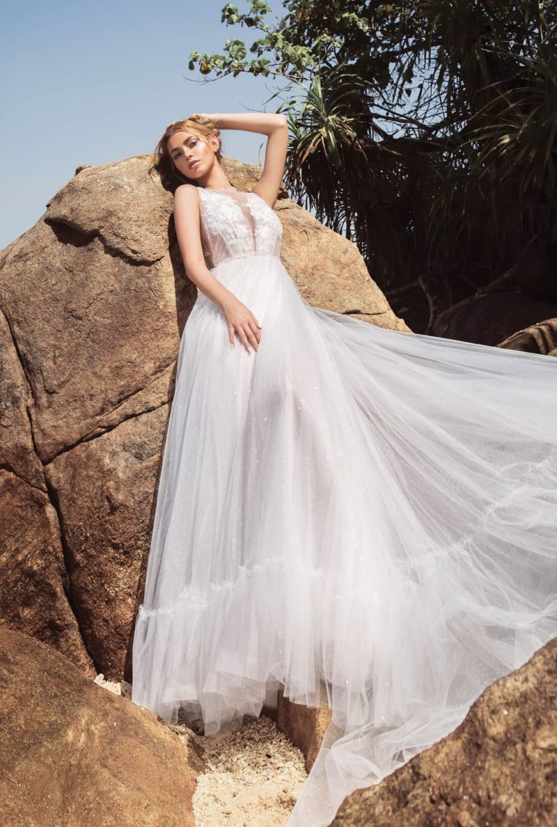 Свадебное платье с открытой спинкой и пышной юбкой, украшенной оборкой.