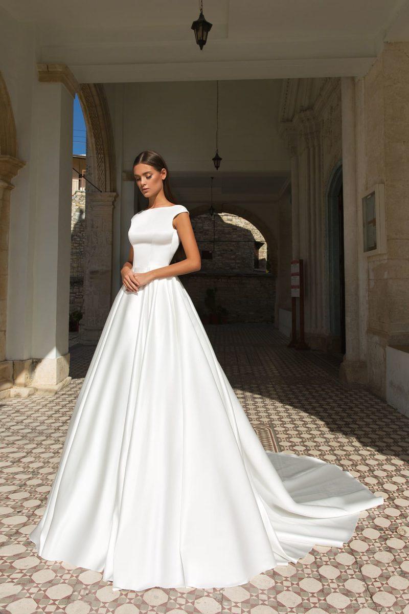 Атласное свадебное платье с открытой спинкой и пышной юбкой.