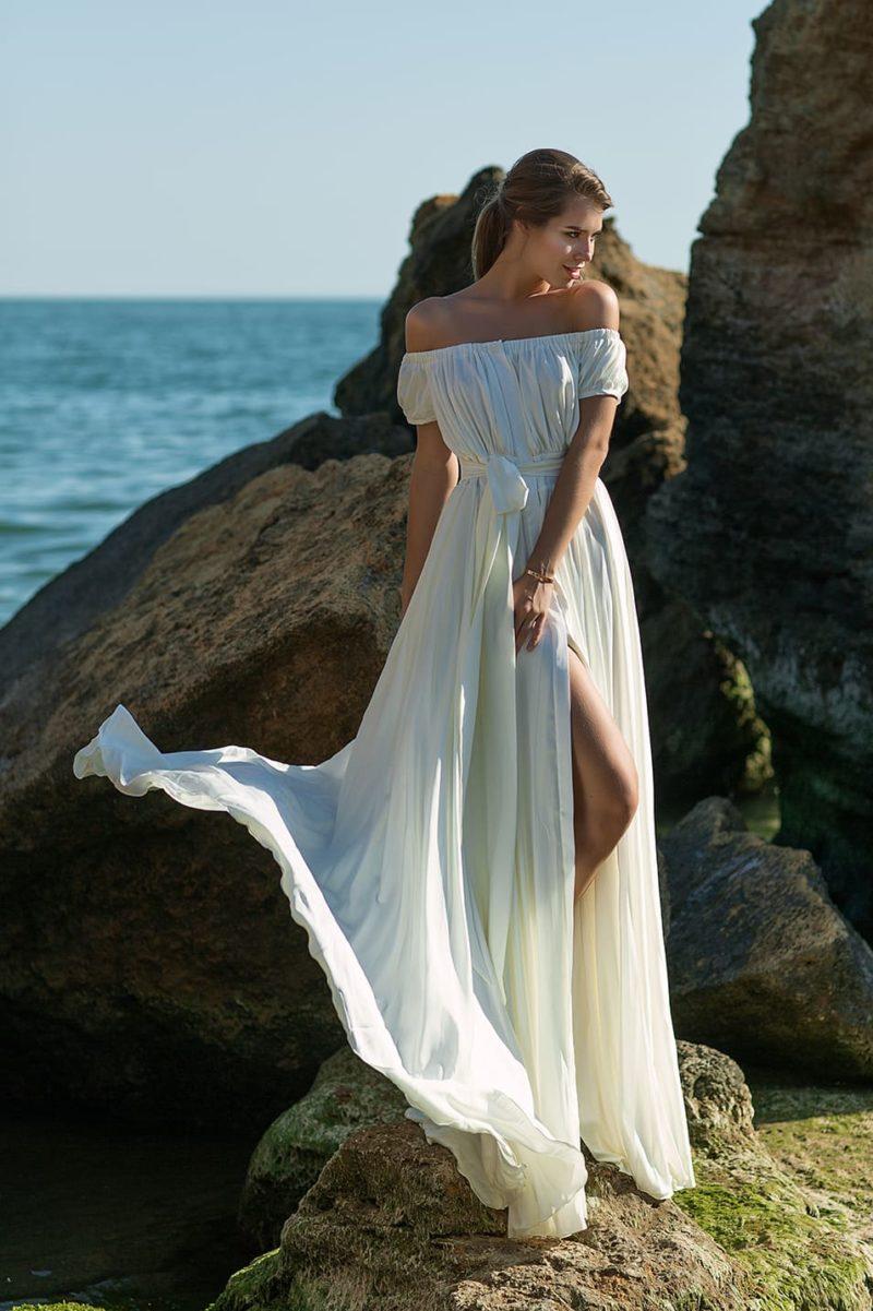 Необычное свадебное платье с пышным рукавом и разрезом на юбке.