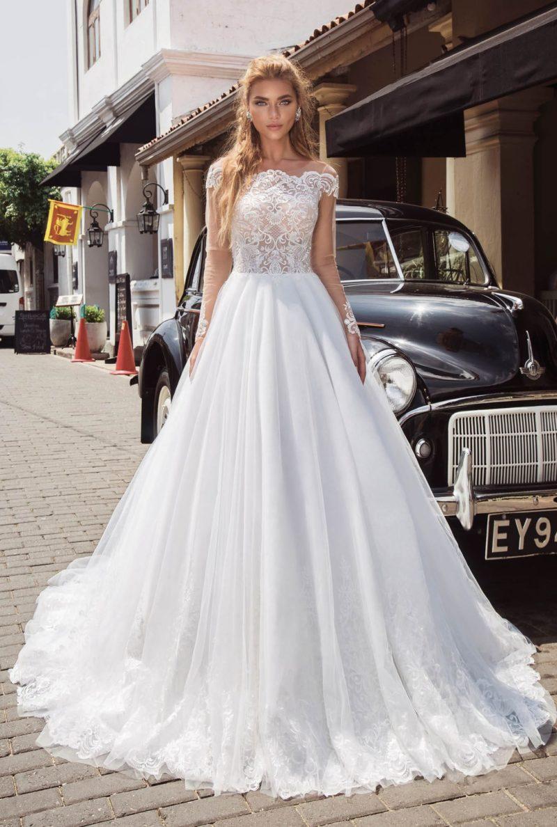 Свадебное платье с портретным декольте и многослойным подолом.