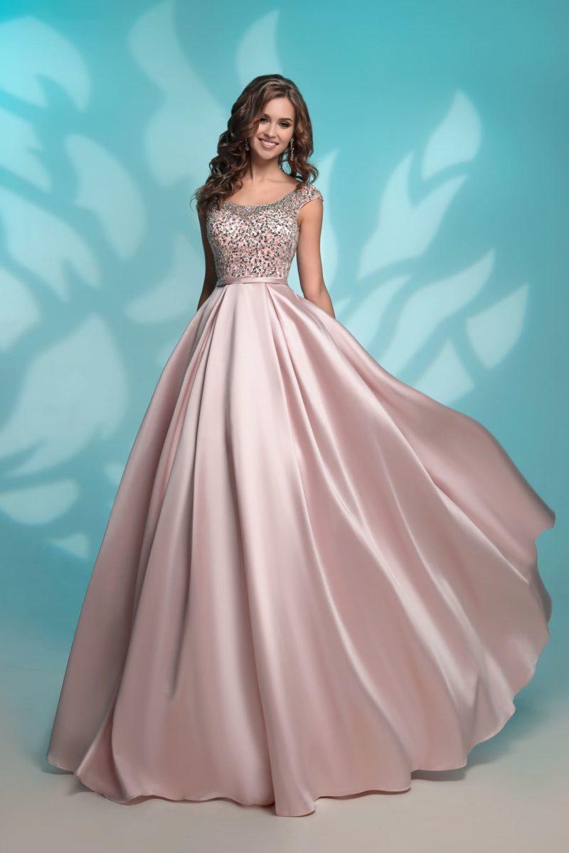 Розовое вечернее платье с округлым вырезом и декором из стразов.