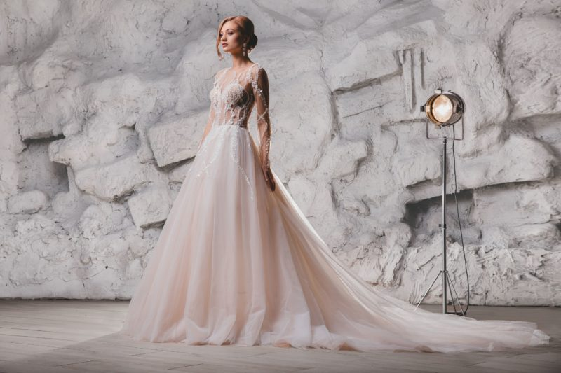 Пышное свадебное платье с длинным рукавом и нежной отделкой.