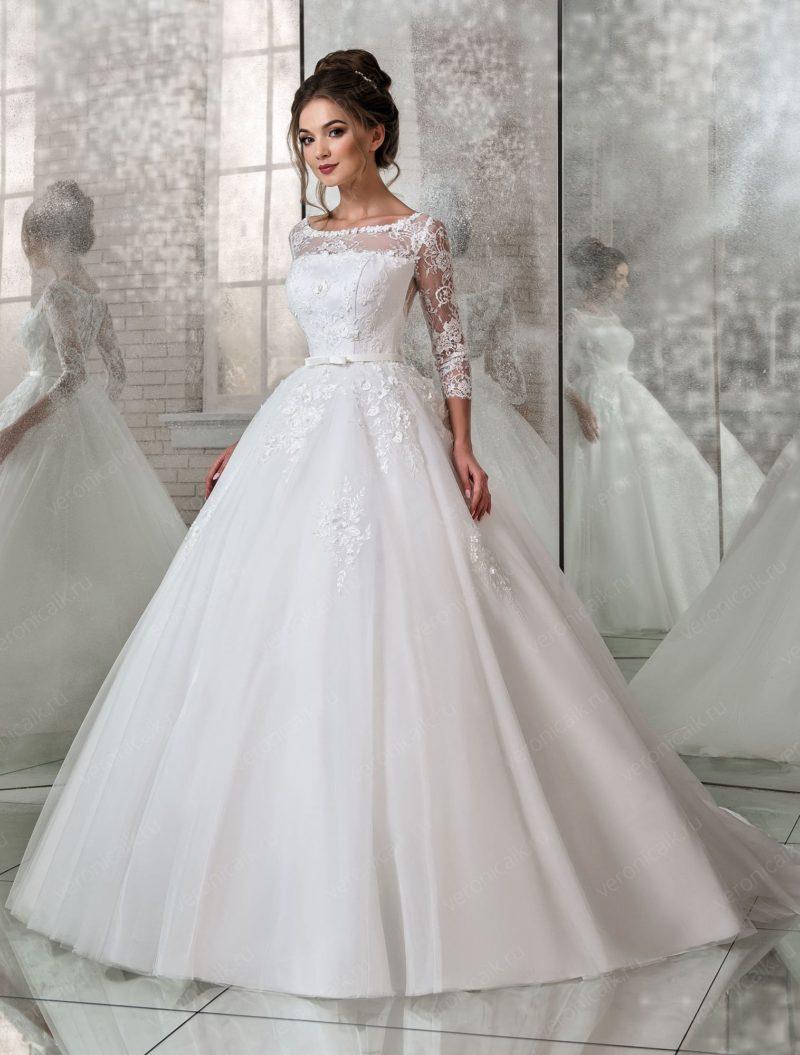 Пышное свадебное платье с длинным рукавом и поясом с бантом.