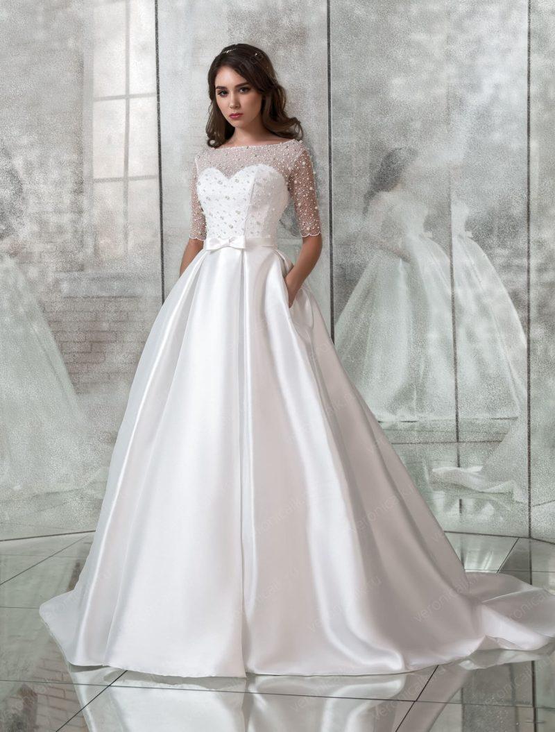 Атласное свадебное платье с бисерным декором и скрытыми карманами.
