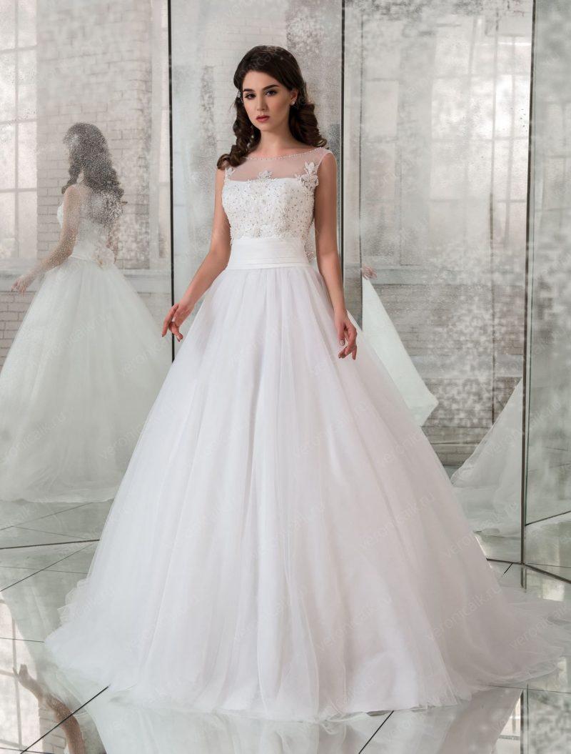 Пышное свадебное платье с закрытым лифом и широким поясом.