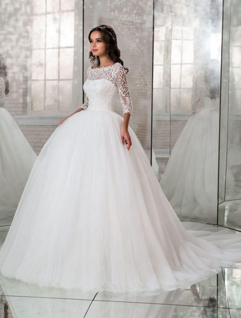 Пышное свадебное платье с открытой спинкой и полупрозрачным шлейфом.