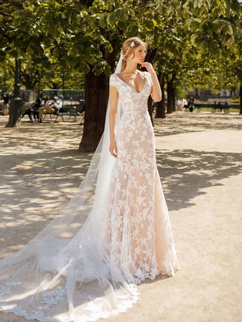 Бежевое свадебное платье с глубоким вырезом и верхней юбкой.