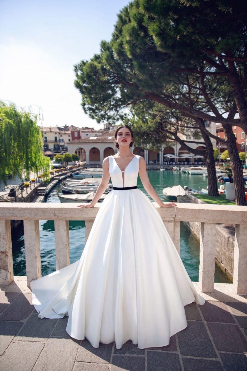 Пышное свадебное платье с черным поясом и длинным шлейфом.