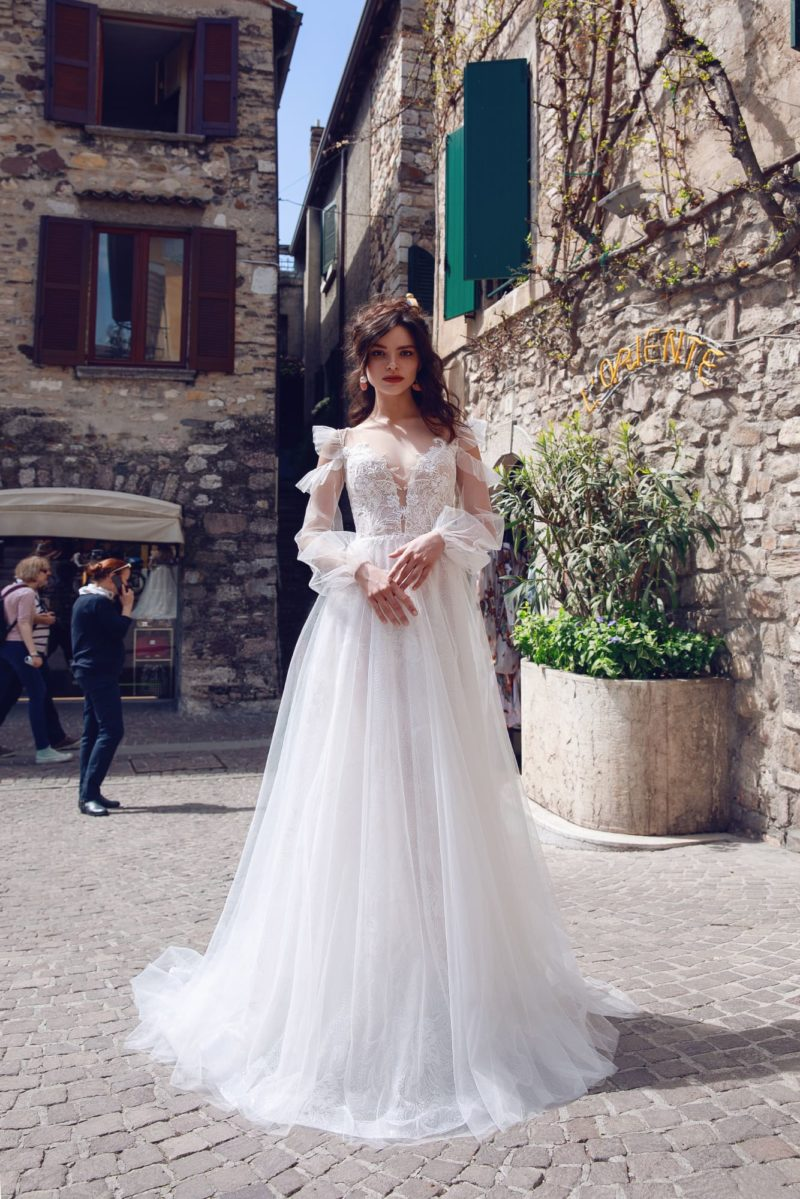 Свадебное платье с длинным пышным рукавом и многослойной юбкой.