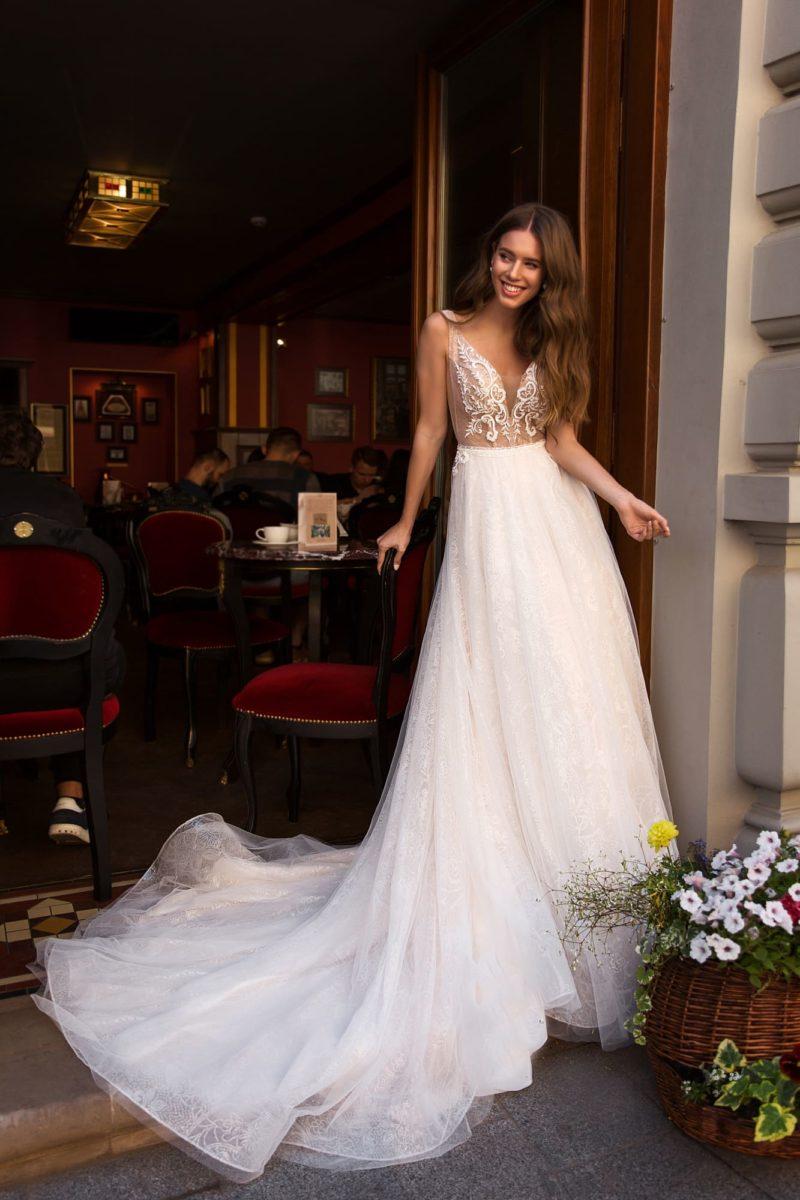 Свадебное платье с многослойной юбкой и глубоким вырезом на лифе.