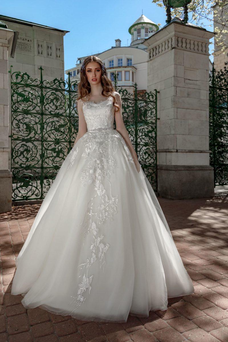 Пышное свадебное платье, оформленное глянцевым кружевом.