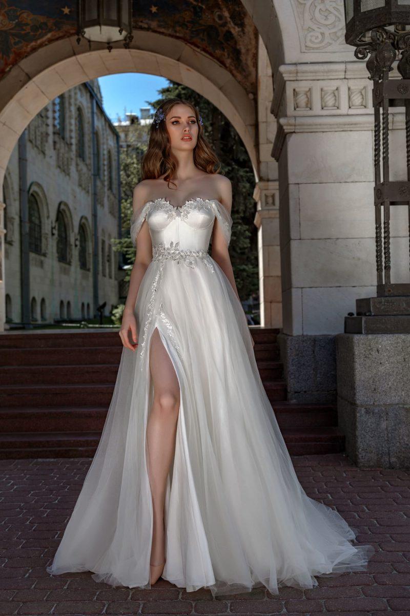Пышное свадебное платье с открытым фигурным лифом и разрезом.