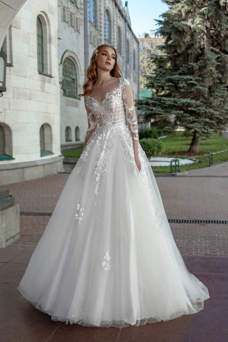 Пышное свадебное платье с длинным рукавом и бежевым корсетом.