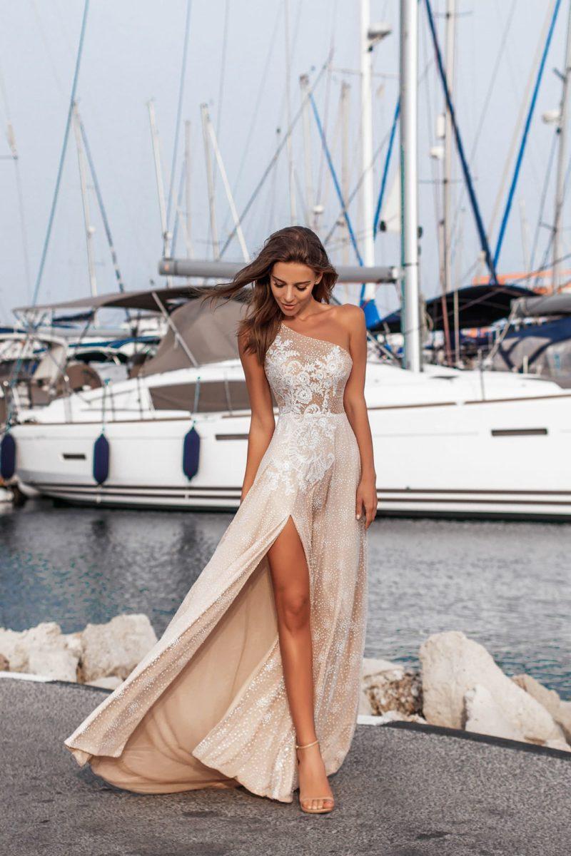 Бежевое свадебное платье с асимметричным лифом и разрезом на юбке.