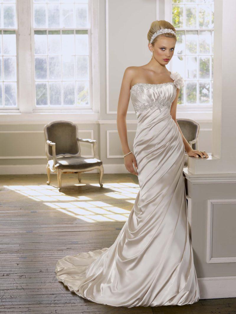 Глянцевое свадебное платье с лифом прямого кроя и пышным бутоном сбоку на плече.