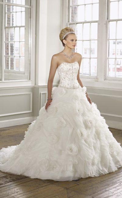 Открытое свадебное платье с бисерной вышивкой на лифе и пышным декором юбки.