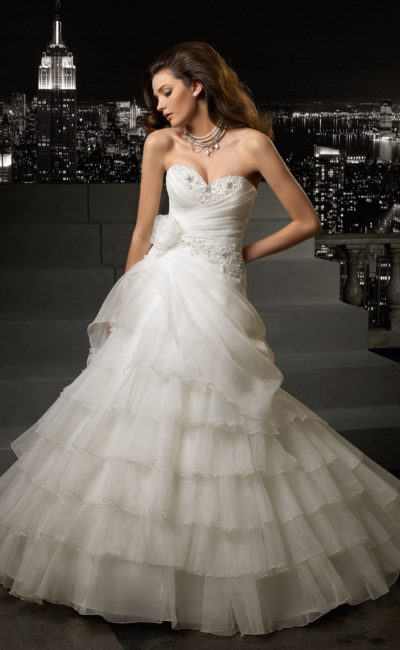 Роскошное свадебное платье с лифом в форме сердца, украшенным бисером, и многоярусной юбкой.