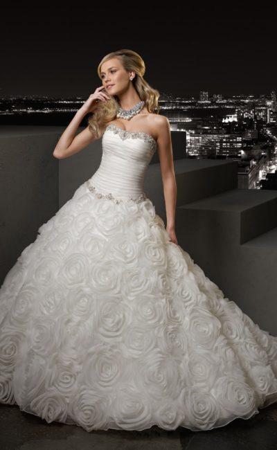Роскошное свадебное платье с лифом прямого кроя и пышной отделкой юбки со шлейфом.