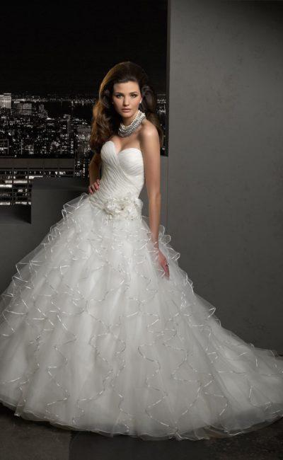 Пышное свадебное платье с открытым лифом и полупрозрачными оборками по всей длине юбки.