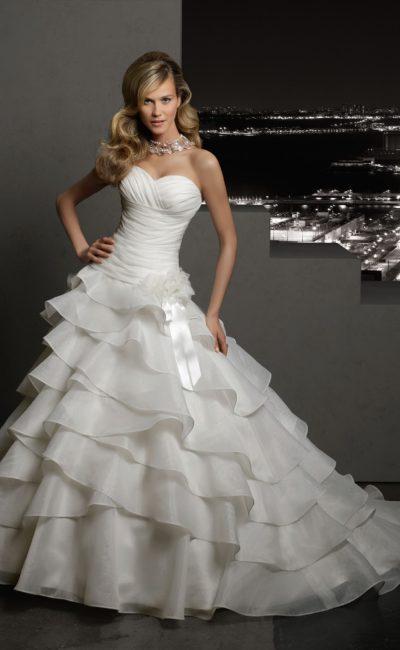 Открытое свадебное платье с лифом в форме сердца и пышными оборками по юбке со шлейфом.