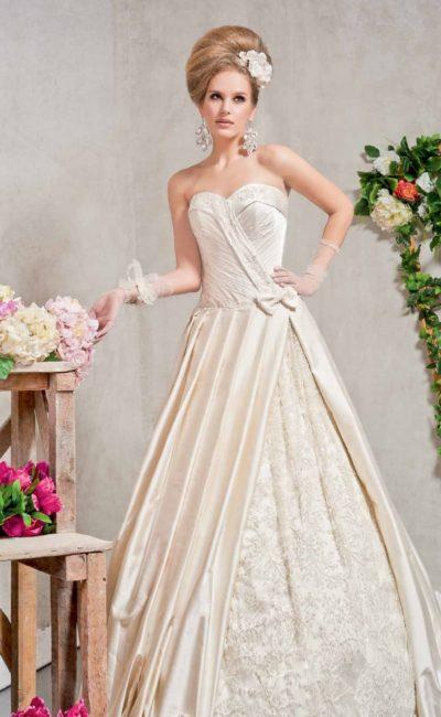 Кремовое свадебное платье с атласными драпировками и открытым вырезом.