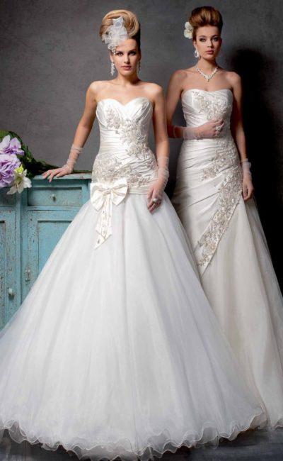 Изысканное свадебное платье пышного кроя с заниженной линией талии и атласным лифом.