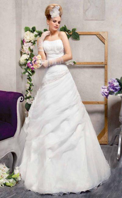 Романтичное свадебное платье с воздушным подолом, покрытым нежными драпировками.