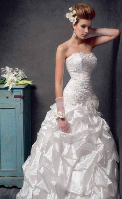 Драматичное свадебное платье с открытым лифом и глянцевыми объемными оборками по юбке.