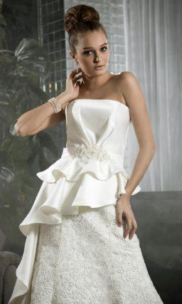 Фактурное свадебное платье с асимметричной баской и открытым декольте.