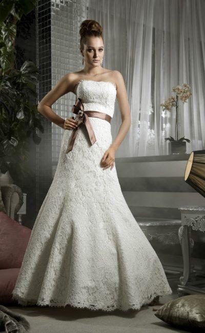 Кружевное свадебное платье облегающего кроя, дополненное коричневым атласным поясом.