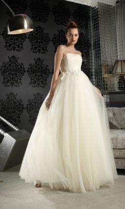 Свадебное платье цвета «слоновой кости», с открытым корсетом и многослойной пышной юбкой.