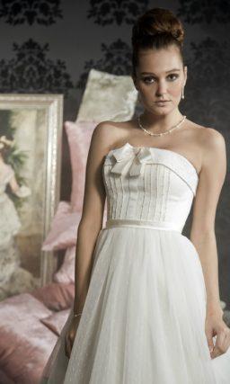 Пышное свадебное платье с горизонтальными полосами отделки по подолу и открытым корсетом.