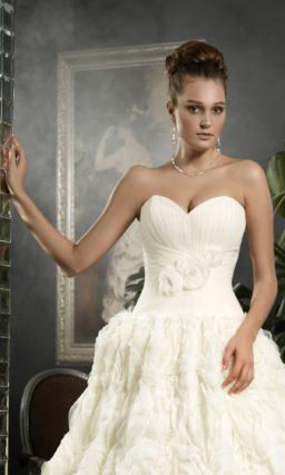 Пышное свадебное платье с объемной отделкой юбки и эксцентричной накидкой.